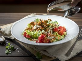 A colorful salad in a deep plate drizzled with a light dressing.