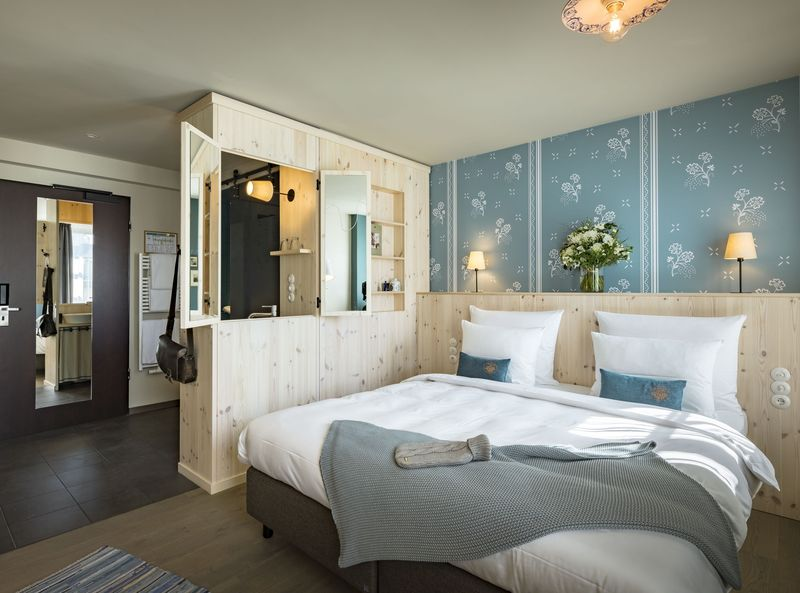 The room Gundi in the Marias Platzl Hotel in Munich with in shades of blue and a comfortable double bed.